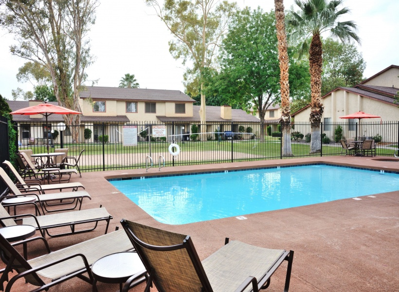 View of Resort-Style Pool, Showing Sundeck, Seating With Umbrellas, and Landscaping at Camelot Apartments